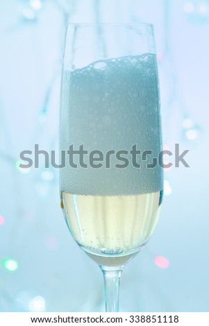 Foam champagne in a flute glass on the festive lights background.