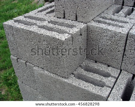 Foam concrete construction blocks with holes stacked outdoor on grass.                                - stock photo