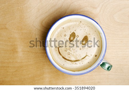 Foam form of smile face in cup of Cappuccino Coffee on wooden table. - stock photo