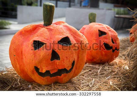 Foam Halloween pumpkins on haystack in Halloween theme restaurant - stock photo