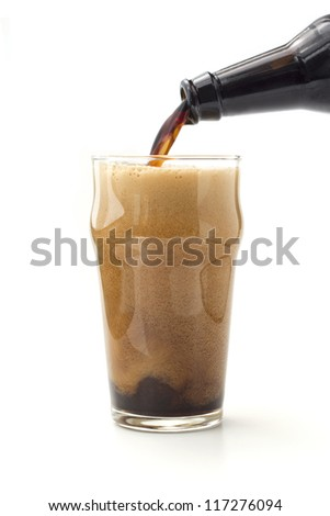 foam of dark beer poured from bottle on white background - stock photo