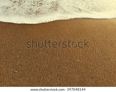 Foam of wave and yellow sand beach, high tide, warm sea and sand beach, summer vacation by the sea, seaside travel photo, foam and sand, warm sand on the beach, calm sea, Bali, Indonesia - stock photo