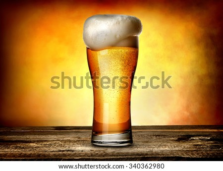 Foam on beer in glass on a wooden table - stock photo