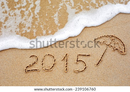 Foaming sea wave coming to wash inscription of the year 2015 written in the wet yellow beach sand. Concept of celebrating the New Year at some exotic place - stock photo
