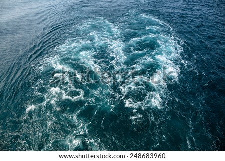 Foamy track behind big ship on the blue sea  - stock photo