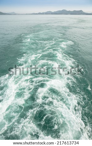 Foamy track in green sea behind the stern of the ship overlooking the coast - stock photo