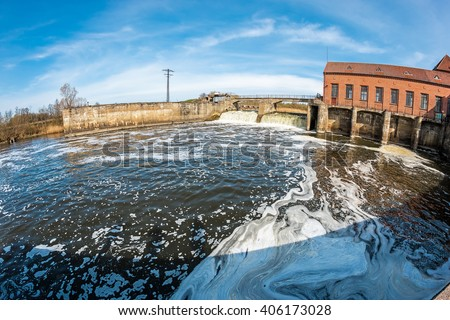 Foamy water in the reservoir of the old abandoned hydroelectric power station - stock photo