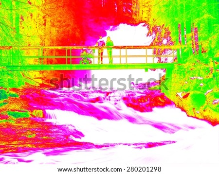 Foamy water level of waterfall, bellow footpath bridge with people. Cold water of mountain river in infrared photo. Amazing thermography.  - stock photo