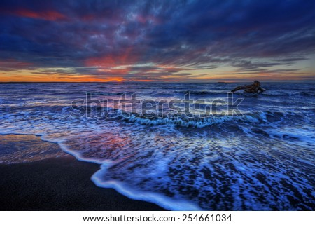 Foamy waves breaking onto a beach at dusk, under intensely dark clouds.  - stock photo