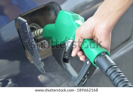 focus  at hand refilling the car with fuel on a filling station