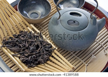 Focus at the dry oolong tea with a set of oriental teapot and cups. - stock photo