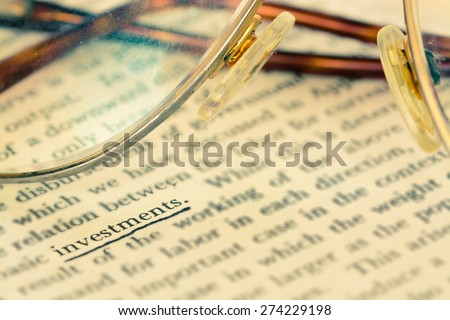 Focus investment word in vintage text book  - stock photo