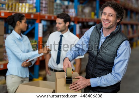 Focus of manager is smiling and posing during work with his colleagues in a warehouse