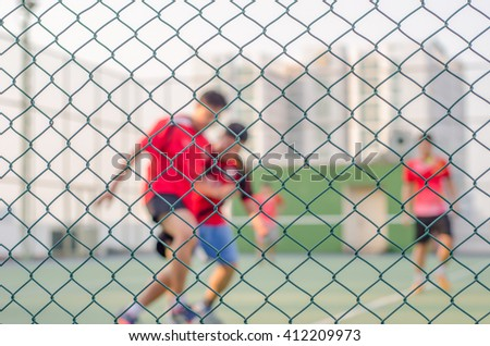 Focus of wired fence and blur image of People are playing futsal. Exercise after work