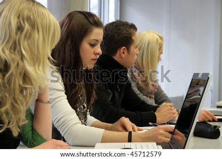 Focus on a row of young international students listening to a lecture - stock photo