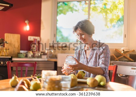 Focus on a woman holding a old fashioned glass jar in a luminous kitchen, sitting at a wooden table with pears and utensils around her, to make rustic jar of fruits. Blur background. Shot with flare - stock photo