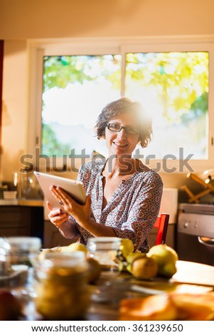 Focus on a woman with glasses looking at camera, holding a tablet in a red kitchen. She is sitting at a wooden table with fruits and old fashioned jar around her. Blur background, shot with flare - stock photo