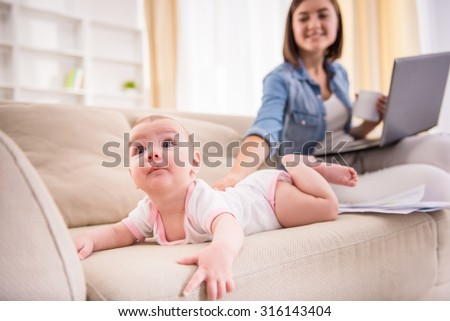 Focus on baby girl lying on the couch while her mom is sitting near with laptop. - stock photo