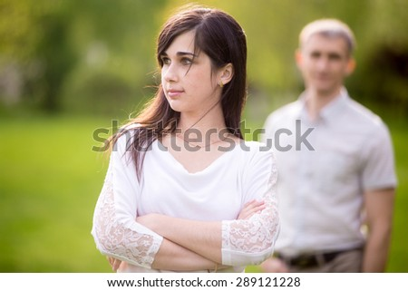Focus on beautiful young woman with sad or serious expression standing with crossed arms, young man on the background looking at her. Love problems, unhappy couple after an argument concepts - stock photo