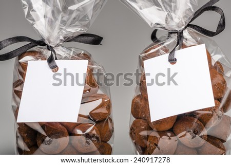 Focus on blank label on two luxury plastic bags with elegant black ribbons of chocolate truffles for gift. You can add your own trademark or your own message. Shooting on grey background in studio. - stock photo