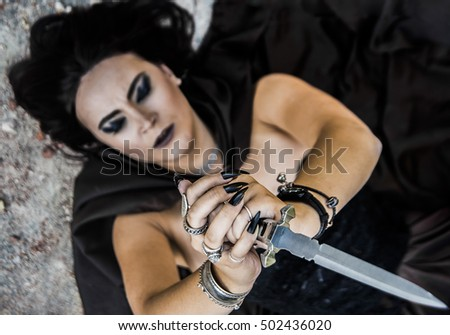 focus on fingers. Sexy dangerous witch woman in black dress with one magical knife. Girl lie on floor