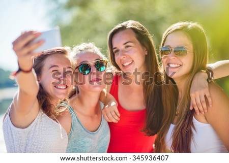 Focus on four girlfriends taking selfies on a smartphone and posing arm in arm during a sunny day. They are wearing summer clothes, hat and sunglasses