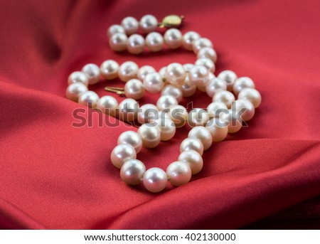 Focus on front of pearl necklace isolated on red satin dress