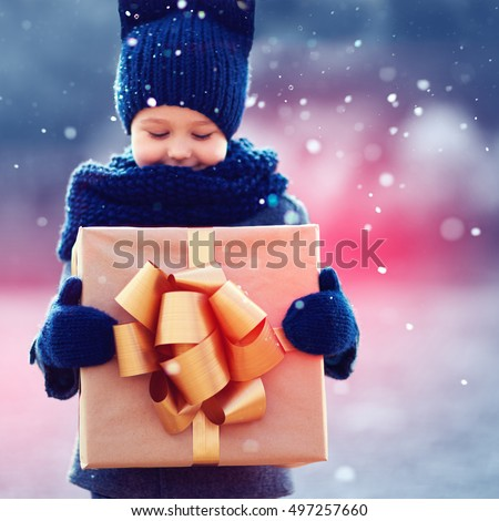 Focus on gift box. Adorable happy kid with big present under a snowfall.