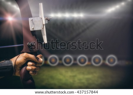 Focus on hand doing archery against football pitch with lights - stock photo