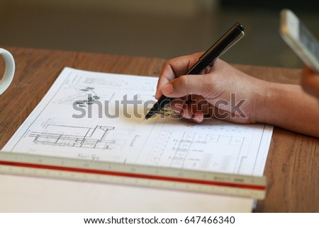 Focus on hand writing In construction meeting room,black pen and scale put on the construction drawing,engineering drawing.