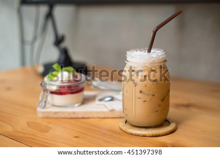 focus on   ice coffee with strawberry panacotta  background
