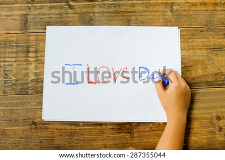 Focus on kid hand use crayon color write text on white paper. I love dad. - stock photo