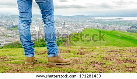 Focus on legs of a female model wearing skinny blue jeans and brown suede boots admiring Edinburgh landscape from the top of the Arthur's seat. Scotland, UK. - stock photo