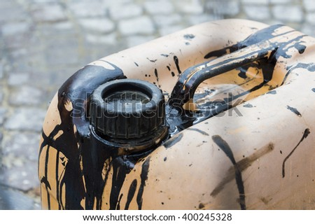 Focus on old jerry can dirty of black petrol - stock photo
