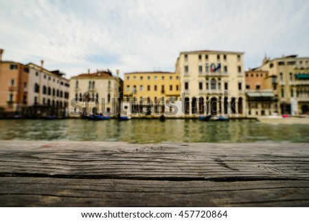 Focus on old wooden pier, water, canal,bridge and traditional buildings as background, Venice,Italy, Europe. - stock photo