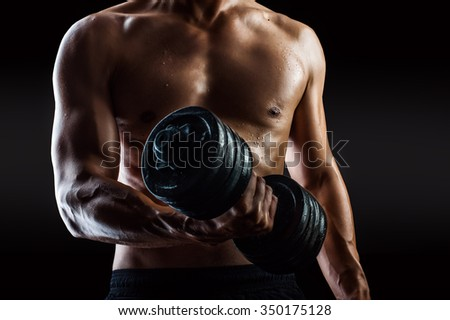Focus on right torso. Dark contrast shot of young muscular fitness man torso and arm. Bodybuilder with beads of sweat training in gym. Working out with dumbbells on black background - stock photo