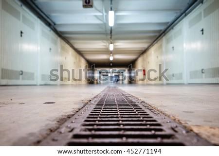 Focus on sewer, Underground parking lot. Basement parking. Car park spaces. Empty parking. Underground passage. - stock photo