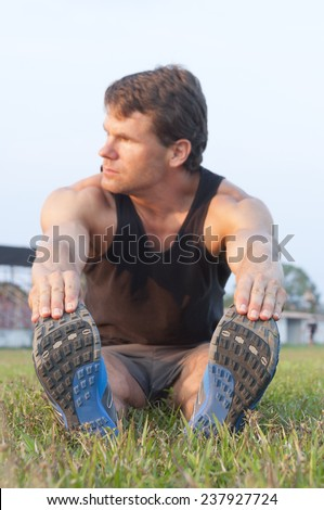 Focus on shoes as muscular Caucasian man sits in grass reaching for toes to do hamstring stretch on grass sport field - stock photo