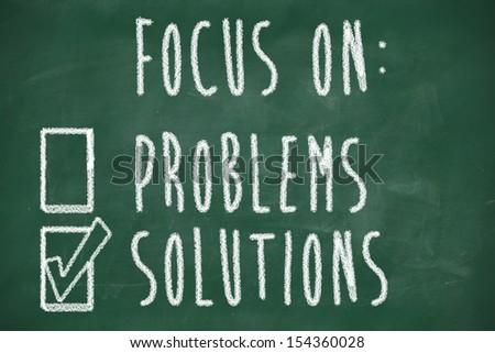focus on solutions concept, handwritten on blackboard - stock photo