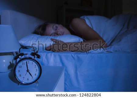Focus on the alarm clock in front of sleeping woman at night in the bedroom - stock photo