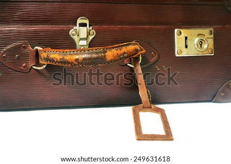 Focus on the lock, handle and label an old suitcase