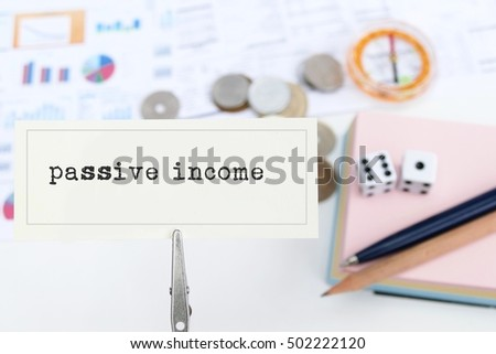 focus on the word passive income text / letter /word with the background of money, dice, pen, compass - the business concept