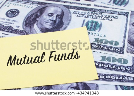 Focus on the words Mutual Funds written on a yellow paper with USD dollars currency as a background. Concepts of investment and business. - stock photo