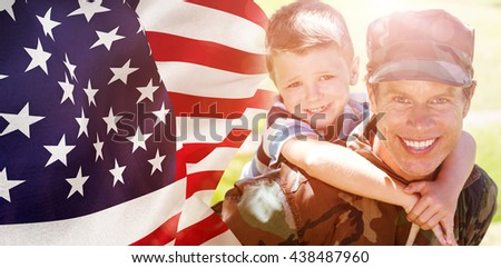 Focus on usa FLAG against happy soldier giving piggyback to his son - stock photo