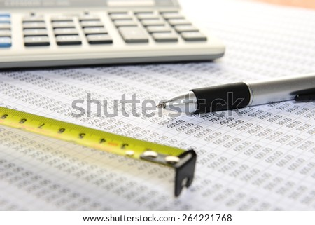 Focus pen, calculator and pen and measuring tape on sheet number - stock photo