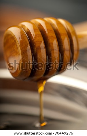 Focus play with wooden honey dipper - stock photo