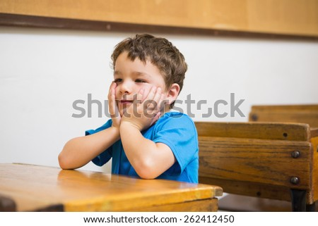 Focus pupil sitting at his desk at the elementary school