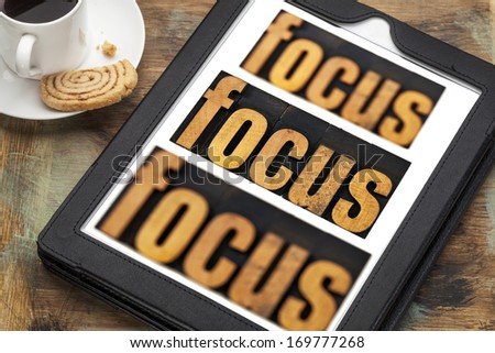 focus word in and out of focus  - text in vintage letterpress wood type on a digital tablet with a cup of coffee