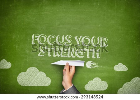 Focus your strenght concept on black blackboard with businessman hand holding paper plane - stock photo