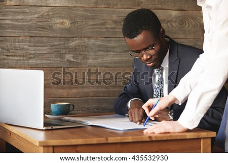 Focused African American businessman checking papers with his personal assistant in white shirt. Young female colleague points at lines in documents, explaining details in a business contract. - stock photo